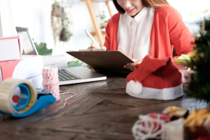 woman checking her emails with christmas decorations