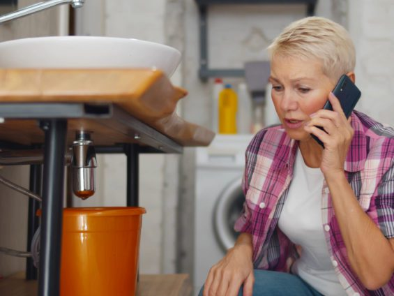 woman calling a plumber because of a leak